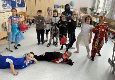 Pomieszczenie świetlicy, grupa dwanaściorga dzieci w strojach karnawałowych. Dwóch chłopców leży z przodu, pozostałe dzieci stoją.