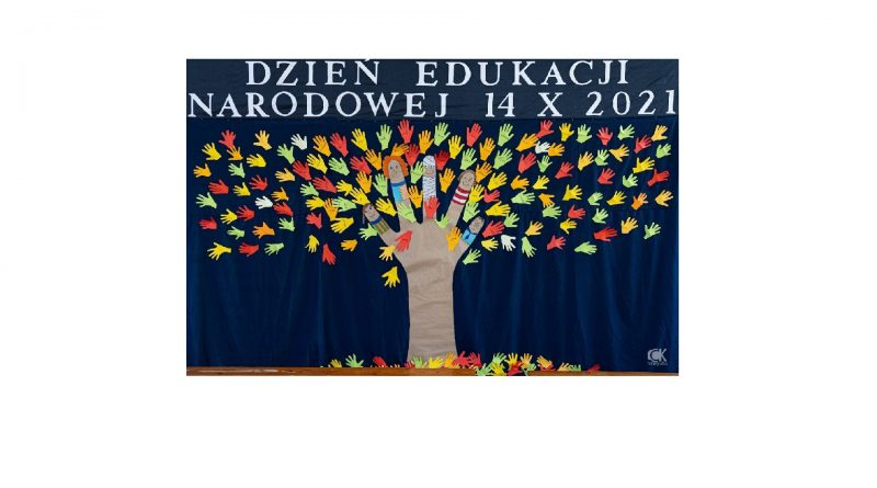Na granatowym tle napis Dzień Edukacji Narodowej 14X 2021, pod spodem drzewo: pień - ręka z palcami w kolorowych ubraniach, na których są twarze dzieci (jeden palec jest owinięty bandażem), liście na drzewie i pod drzewem to przyklejone kolorowe dłonie.